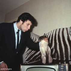 25 year old Welsh singer Tom Jones with his pet Siamese cat 'Elvis' in London. 25th February 1965