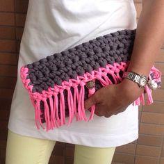 ダークグレーでベースを編み、蛍光ピンクで縁取りとフリンジをつけました。ボタンにかけて開閉します。サイズは、蓋を閉じた状態で、縦約17㎝×横約32㎝×厚み約4㎝です。長財布と携帯、ハンカチティッシュがちょうど入るくらいの大きさです。歩くたびにフリンジが揺れ、蛍光ピンクなので、ナツにぴったりのクラッチです。