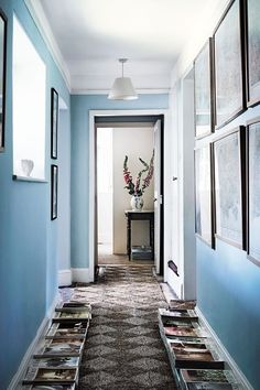 Pale Blue Landing in Hallway Design Ideas. The landing has been painted blue and is home to piles of magazines.