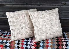 The pattern: A Cushion Cover of Cozy Distinction and Amazing Generosity.    This oversized pillow cover front is a sculptural kaleidoscope of shapes and textures, created with deep symmetrical cables. The look is versatile for any decor. Two versions are included, to make a matching but slightly different pair.