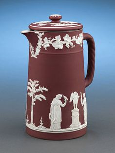 "A lovely crimson jasperware jug by Wedgwood, featuring an applied white jasper neoclassical decoration of acanthus leaves and grapes bordering the rim. Maidens, children, and foliage provide the main focal point on the body. A twisted jasper handle and original lid complete this great jug. Jasperware is one of Wedgwood's crowning achievements, and is highly acclaimed for revolutionizing ceramic art. Marked ""WEDGWOOD / ENGLAND""Circa 19208 1/2"" high"