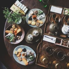 Rustic and moody fall table setting with earthy ceramic plates, rattan trays, greenery and fab looking food.  Photography by: NATHANAELYAU.VSCO.CO