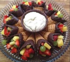 Fruit desert-Ice cream cones dipped in chocolate and filled with fruit. Server with fruit dip in center.