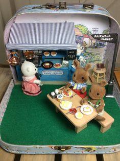 Beaufort & Wildwood Hot Food Stall, suitcase diorama. Featuring Sylvanian Beaufort Polar Bear and Wildwood Rabbits. A village green market.