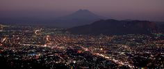 Vista parcial de San Salvador, tomada desde el mirador de la carretera al Boqueron, Volcan de San Vicente al fondo, El Salvador
