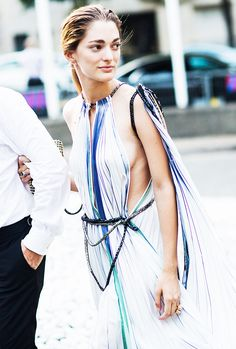 A striped, flowing maxi dress is worn with a statement clutch and cocktail ring