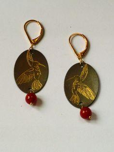 Boucle d'oreilles arrondies serties de perles rouges.
