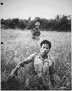 Corporal with the 9th Marines, leads a severely injured Viet Cong soldier to a collection point, October 1965.