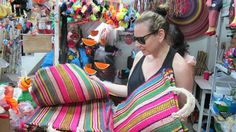 Mexico City - L-atitude's Creative Director Kym Canter selecting woven bags in the Mercado Alvaro Obregon — a not-to-be missed market.