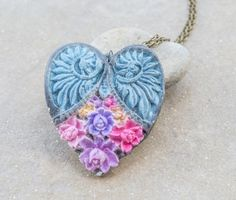 This gorgeous heart necklace with flowers and wings is fully handcrafted. Its made of polymer clay and antique gold chain.  The length is 28 cm