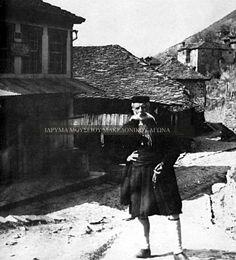 Ολόσωμη αναμνηστική φωτογραφία, η οποία απεικονίζει έναν ηλικιωμένο άνδρα από το Μέτσοβο να ποζάρει σε εξωτερικό χώρο. Ασπρόμαυρη ψηφιοποιημένη φωτογραφία. Συλλογή Αστέριου Κουκούδη