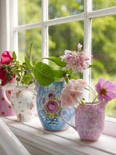 kleurrijke vazen/theepotten als raamdecoratie