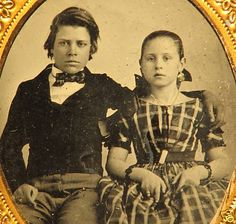 "He might have his arm around sister's shoulder (his hand looks so strong),  but he's not comfortable with it there. The clothes ""tween"" boys wore in the 1840s-50s were really kind of cool. I think sister is wearing mamma's earrings and wristlets, carrying mamma's fan for this picture."