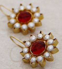 Gold polished silver earring studded with red stone and pearls
