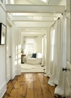 .....all white + wooden floors + low ceiling beams and curtain placement