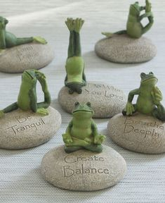 Set of six frog figurines depicts yoga frogs balancing on rocks inscribed with uplifting inspirational phrases.