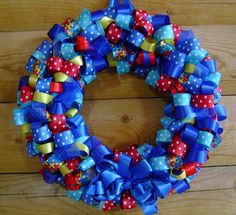 Autism Awareness Blue Wreath -   This colorful ribbon wreath incorporates the colors of the Autism Awareness Jigsaw ribbon. Blue, turquoise, red and yellow. 14 Inches