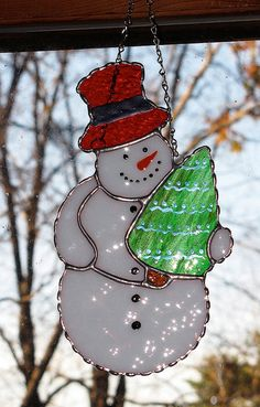 Stylish snowman sun catcher. Semi-transparent white textured glass is used for the snowman, green transparent glass for the tree and deep red