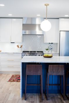 A kitchen reveal for a mid-century modern remodel. White cabinets, navy island, and brass hardware.