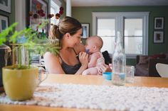 A documentary photograph of a mother feeding her baby during an in home lifestyle family photo session in Boston, Massachusetts - Gina Brocker Photography