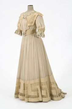 Woman's dress w/ day & evening bodices Suit constructed light yellowish brown wool & yellowish white silk chiffon trimmed w/ lace of embroidered net underlaid w/ cloth  black & gold threads Suit day bodice consists of a tunic length jacket open from waist w/ uneven hemline & train Attached boned bodice dickey has stand-up collar & elbow length full sleeves w/ cuff of wool & lace Slight mono bosom front hook eye snap closure & lined w/ silk taffeta Medium yellow brown velvet piping edges…