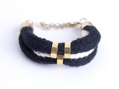 Black and white cord bracelet with gold beads. $35,00, via Etsy.