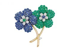 Designed as a pair of blossoming flowers decorated with cabochon sapphires and cabochon emeralds and accented with diamonds, from flared gold stems, mounted in 14k white and yellow gold.