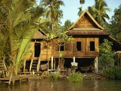 Traditional Thai house on stilts above the river in Bangkok Thailand.