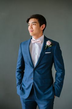 groom in navy wedding suit and pink bow tie