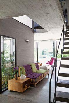 Una casa moderna y ecléctica con estructuras de hormigón a la vista y contraste de color en las superficies textiles de sillones.