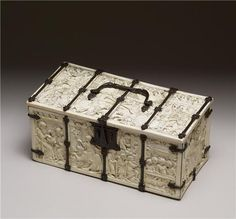 Ivory and bone Casket Box from 1330-1350 (Medieval) carved with scenes from romances and allegorical literature representing the courtly ideals of love and heroism. In the center of the lid, knights joust as ladies watch from the balcony; to the left, knights lay siege to the Castle of Love, the subject of an allegorical battle. Scenes  are drawn from well-known stories about Aristotle and Phyllis, Tristan and Iseult, and tales of the gallant, heroic deeds of Gawain, Galahad, and Lancelot.