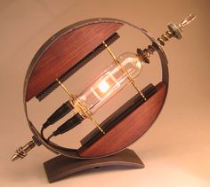THIS LAMP HAS SOLD. My Lamp called Outlook. Shines bright whether turned on or off. A steel band circles glass and wood and electricity.    I