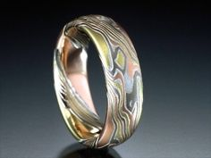 I love the thought of mokume/damascus, especially seeing a layer wrap around from the front to back of a ring. Not thrilled on the thought of 4 different golds, but multi-tone titanium might be do-able...