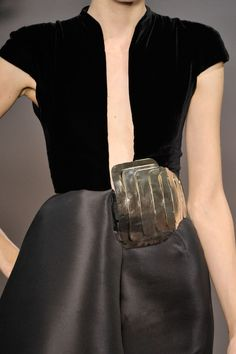 A bold brass adornment at the waist and a sumptuous mix of black fabrics - elegant black dress; couture fashion details // Stéphane Rolland