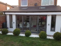 A row of folding doors made of gray aluminum closed and looked from a . - A row of folding doors made of gray aluminum closed and looked from the outside - Folding Doors Exterior, Kitchen Diner Extension, House Design, Bungalow Extensions, House Extension Plans, House Exterior, Open Plan Kitchen Living Room, Exterior Doors, Roof Extension