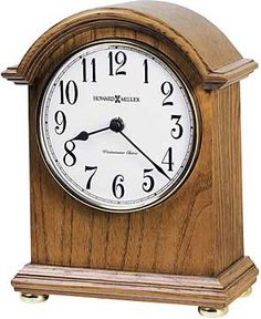 """The Howard Miller Myra 635-121 Mantel Clock is a petite arched mantel clock that features a decorative top molding. An off-white dial under convex glass features black Arabic numerals and black hands. Finished in Oak Yorkshire it has automatic nighttime chime shut-off. Quartz movement plays Westminster melody and strikes on the hour, and features an on/off switch for chime and hour strike. Size: H: 8-3/4"""" W: 7"""" D: 3-1/4"""""""