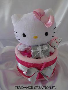 Délicat gâteau de couches composé de couches, plaid, robe, ours en cristal, décorations et une très grande HELLO KITTY Ballerine. Réalisé par TENDANCE CREATION.FR