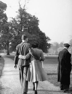 American soldier & his English girlfriend strolling past man watching softball game on a blissful spring evening in Hyde Park. 1944.