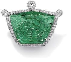 A carved emerald and diamond brooch/pendant. Photo Philips de Pury & Co  The shield-shaped emerald, weighing approximately 135.00 carats, carved with foliate details to front and back and set within a brilliant-cut diamond looped frame, length 4.6 cm, multiple concealed pendant attachments, double pin fitting.