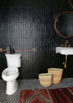 Wellworth toilet   Purist faucet   Soho sink   Glossy black walls ground the    pattern-upon-pattern of the bold floor tile and vintage kilim. Going beyond the typical, a leather, belted mirror elevates the unique feel of this eclectic bathroom.