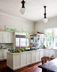 Beautiful kitchen with lots of light.The glass display case on counter is interesting, but it seems like an odd place to put it.