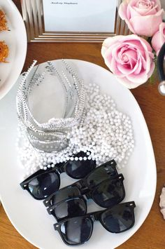 Guests need to look the part, so offer them Audrey Hepburn's classic look from Breakfast at Tiffany's of black sunglasses, lengths of pearls, and shimmering tiaras.