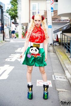 While walking around the streets of Harajuku, we came across twin-tailed Aisaki Mai, the fashion designer for Himitsu Gadget. Mai has been previously featured in our street snaps. Her fierce and colorful street style fashion features resale items such as a Chinese style gold and red embroidered tunic, a green, satin Muay Thai boxing shorts, and YRU platform creepers embellished with sequins, studs and spikes. A Thank You Mart panda crossbody bag and accessories from her own brand Himitsu…