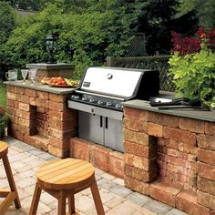 A peninsula of tumbled cast-concrete blocks and a stone counter turns a freestanding grill into a built-in. DIY this setup for about $350 by stacking blocks on a bed of tamped drainage stone, securing each block with masonry glue. | Photo: Jessie Walker/Cornerhousestock | thisoldhouse.com