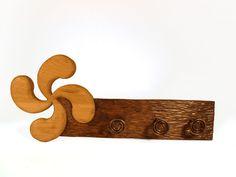 Perchero con lauburu tallado en madera de roble en altorrelieve, tratado con betún judaico a dos tonos con tres perchas de hierro artesanales.  Dimensiones:60×25cm.aprox.