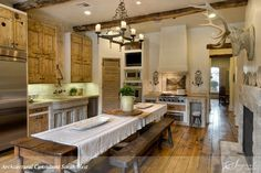 Rustic kitchen. Love the table!!!, sink, stove, beams, fireplace, floor. Not overly crazy about the cabinets or the deer head though.