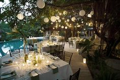 dreamy poolside dinner wedding reception lit by hanging lanterns #TropicalOccasions