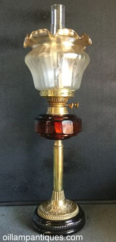Make no mistake, this is definitely a relatively modern reproduction banquet lamp. Regardless of that, it is still a lovely lamp. At first glance the font looks to be ruby glass but once the light is behind it, you can see that it is more like amberina. Either way, it is a lovely colour. The stem and base cap of the banquet lamp are brass and the base itself is black enameled ceramic. The etched and amber tipped shade was made by Vianne Glass, France sometime before 2005 when the business…