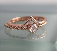 14k SOLID Rose Gold twisted band. 1.5mm thick and paired with a tube bezel set 4mm rose cut Charles and Covard moissanite stone. Shown with 1mm square Chevron Band also in rose 14k recycled gold. This pair makes a beautiful modern set. Can be made in any size, 1/2 size or 1/4