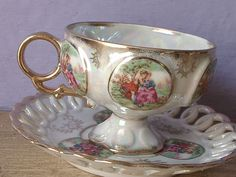 This beautiful, shimmering set has panels all around the tea cup that are raised and have the image of the Fragonard style couple.